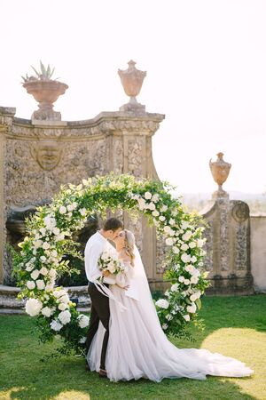 Wedding at an old winery villa in Tuscany, Italy. Round wedding arch decorated with white flowers and greenery in front of an ancient Italian architecture. The wedding couple is kissing.