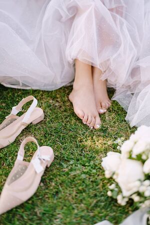 Bare feet of the bride on the grass, next to shoes and a bouquet. Wedding in Florence, Italy, in an old villa-winery. 免版税图像