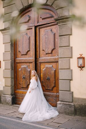 Beautiful bride in a big white wedding dress and long veil is standing in front of huge wooden vintage doors of an old Italian villain Tuscany, Florence. 免版税图像