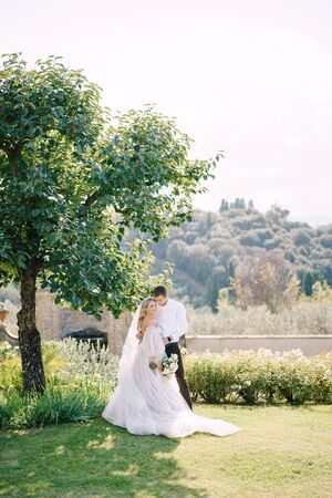 Wedding in Florence, Italy, in an old villa-winery. Bride and groom in the shade of a tree. Wedding couple walks in the garden. 免版税图像