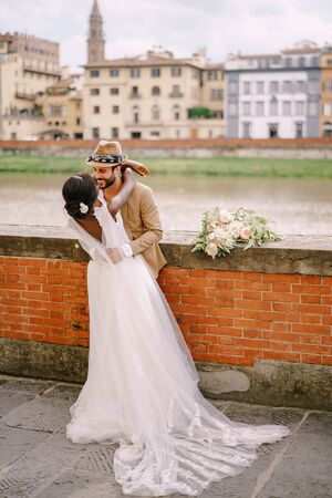 Interracial wedding couple. Wedding in Florence, Italy. African-American bride and Caucasian groom stand embracing on the embankment of the Arno River, overlooking the city and bridges.