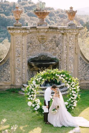 Wedding couple kisses. Wedding at an old winery villa in Tuscany, Italy. Round wedding arch decorated with white flowers and greenery in front of an ancient Italian architecture.