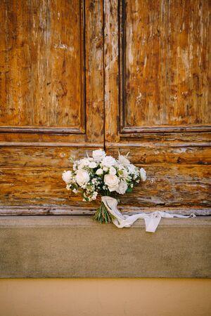 White brides bouquet on a wooden background. Reklamní fotografie