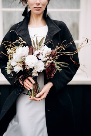 Portrait of a bride in a white silk wedding dress and a black coat with a brides bouquet in her hands. Black wooden house with a white window. Snowing. Destination Iceland wedding.