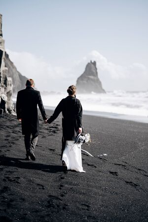 Destination Iceland wedding. A wedding couple walks along the sandy black beach of Vik, near the basalt rock, in the form of pillars. The bride and groom hold hands and walk along the shore.