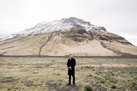 Groom in a black coat on a background of a mountain with a snowy peak. Destination Iceland wedding.