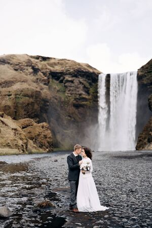 Destination Iceland wedding. Wedding couple near Skogafoss waterfall. The bride and groom are hugging near the river.