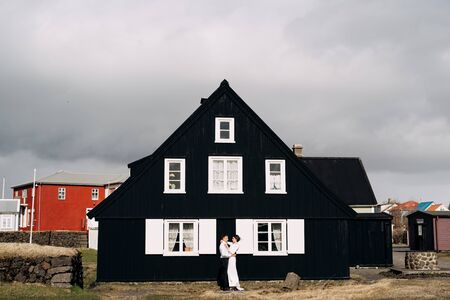 Destination Iceland wedding. Wedding couple near a black wooden house with white windows and shutters. The groom hugs the bride.