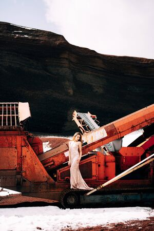 Portrait of a bride model in a golden wedding evening dress, in a yellow-red sandy quarry, in the crater of a volcano in Iceland, Golden Circle. The bride walks near the career vibrating screen. Banco de Imagens