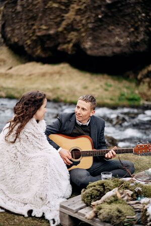 A wedding couple is sitting on the shore of a mountain river, at a table for a wedding dinner. The groom plays and sings for the bride. Destination Iceland wedding, near Kvernufoss waterfall.