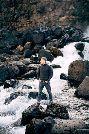 A guy in a black knitted sweater stands on rocks near Ehsaraurfoss Falls, Ehsarau River, National Park, Tingvedlir, Syudurland Region, Iceland. 写真素材