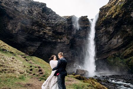 Destination Iceland wedding, near Kvernufoss waterfall. Wedding couple is standing near the waterfall. The groom hugs the bride. Stok Fotoğraf