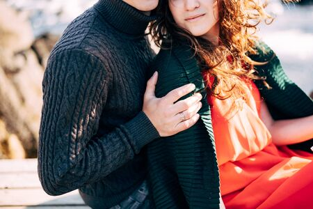 A guy in a knitted sweater tightly hugs a girl in a red dress and a green sweater over his shoulders. Banque d'images