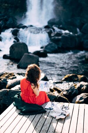 The girl artist paints a picture in the album with watercolors. Near Ehsaraurfoss waterfall, Ehsarau River, Thingvedlir National Park in Iceland. Stock fotó