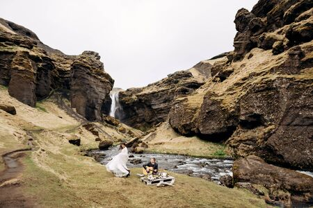 Destination Iceland wedding, near Kvernufoss waterfall. The groom plays the guitar sitting on the grass at an impromptu wedding table, the bride in a white dress and a woolen blanket - dancing nearby