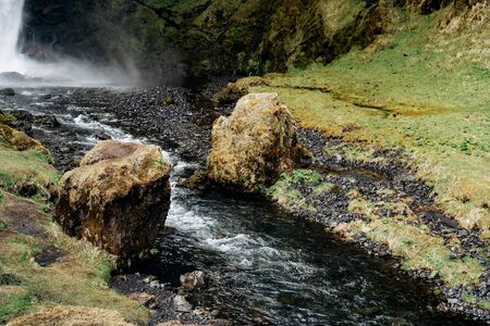 A small mountain river flows between two boulders in the mhu, from the waterfall Kvernufoss in Iceland.