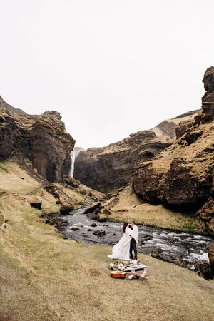 Destination Iceland wedding, near Kvernufoss waterfall. A wedding couple stands under a plaid near a mountain river. The groom hugs bride. They built an impromptu wedding table with decor and guitar Banco de Imagens