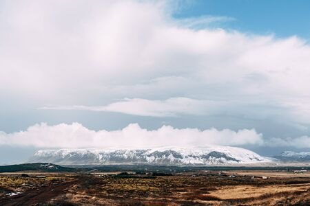 A wide field of dry yellow grass and a mountain in the distance with a snow-capped peak, against a blue sky with white clouds in Iceland.