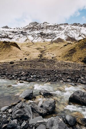 Mountain river at the foot of the mountain with a snow-capped peak. Yellow dry grass on the mountains in May in Iceland.