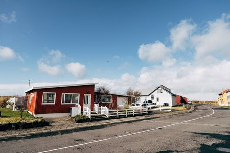 A red apartment building with white windows and a fence, on the street of a residential area where Icelanders live. Asphalt road in a sleeping area. Blue sky with white clouds. Stock fotó