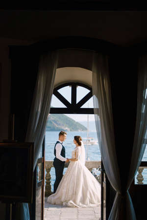 The bride and groom are standing on the balcony of the hotel overlooking the sea, a look through the open old window. Fine-art wedding photo in Montenegro, Perast.