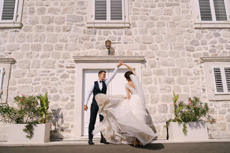 Fine-art wedding photo in Montenegro, Perast. The bride and groom are dancing against the backdrop of an old white house.