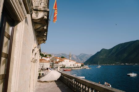 Fine-art wedding photo in Montenegro, Perast. A wedding couple on the hotel terrace with panoramic views of the old town of Perast, the groom circles the bride with a long dress on her hands.