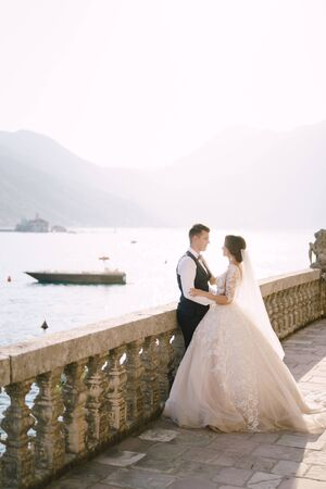 The bride and groom are standing on a large terrace with stone columns, overlooking the Bay of Kotor and the island of St. George and the Island of Gospa od Skrpela at sunset in the old town of Perast