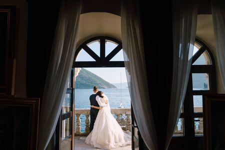 Wedding couple stand on a hotel balcony with sea view, view through an open antique window. Fine-art wedding photo in Montenegro, Perast.