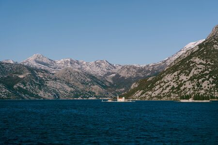 The island of St. George and the Island of Gospa od Skrpela in Kotor Bay, near Perast, Montenegro, against the backdrop of snow-capped mountains in winter.