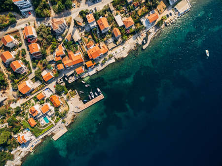 Aerial drone photo, top view - villas, houses and hotels on the beach in Montenegro, the Adriatic Sea.