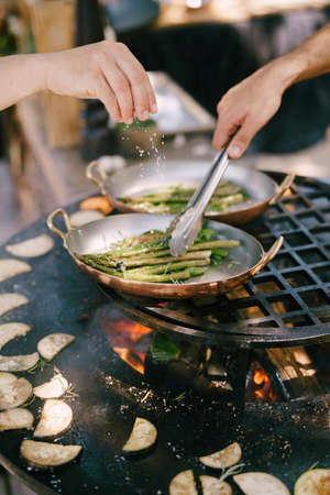 Chefs cook asparagus and eggplant on the grill.