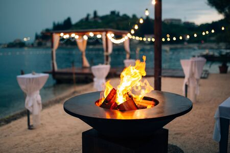 Grill with flames inside. Round table-cooking surface. On the beach, in the background of the gazebo by the water with garlands, in the twilight light. Archivio Fotografico
