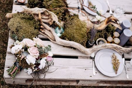 bridal bouquet of white roses, brunia and leucadendron , bouquet of dried lavender on the romantic outing with table decoration, candles, dried branches and moss in Iceland. High quality photo