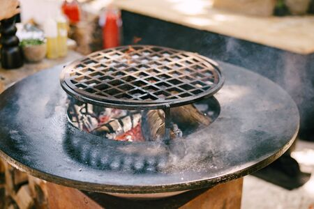 Round grill with flat roasting. Round grille in the center with a fire.