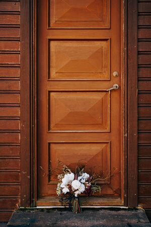 bridal bouquet of white roses, lily, burgundy cloves, protea, dried branches, brunia and leucadendron with grey and black ribbons near the concise wooden door in Iceland. High quality photo