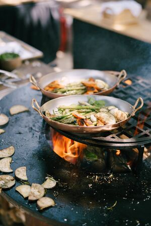 Grilled vegetables. - asparagus, zucchini, carrots and eggplant grilled round-shaped bowl with open fire in the center.