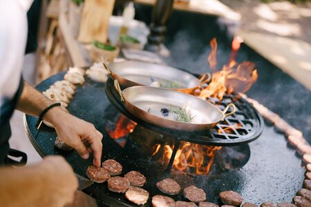 The chef grills meatballs for mini burgers on the grill.