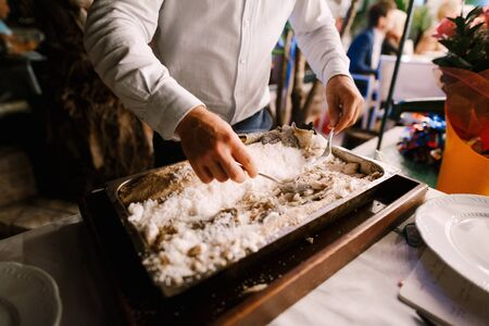 The chef chops the fish baked in salt.