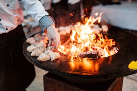 The chef roasts fish steaks on the roasting table.