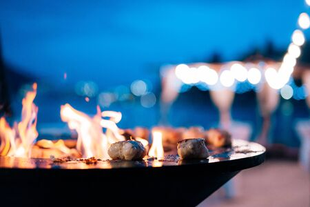 Close-up of pieces of fish fillet on a bowl-shaped grill with a fire hole in the center.