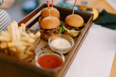 Three mini burgers on a tray with two sauces and fries.