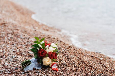 bridal bouquet of white, read and cream roses, ornithogalum, eryngium with white ribbons on the beach near water and wedding rings Banque d'images