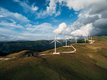 The prospect of a number of high industrial wind turbines on the hill, against the blue sky and velvet white clouds. Stockfoto