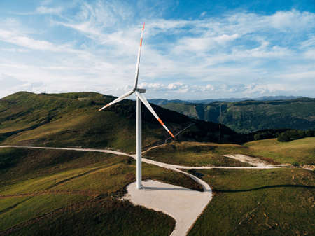 Beautiful bright photo of the wind generator in the field with the road. Stok Fotoğraf