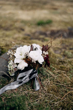 bridal bouquet of white roses, lily, burgundy cloves, protea, dried branches, brunia and leucadendron with grey and black ribbons near the dried grass
