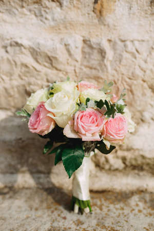 bridal bouquet o fwhite and pink roses and artemisia, with white ribbons near the brick wall. High quality photo