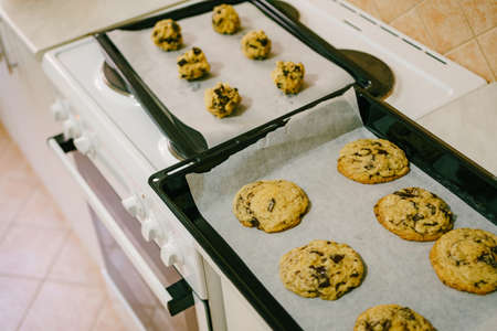 Two baking trays on the kitchen table - with cooked American cookies and raw dough balls.