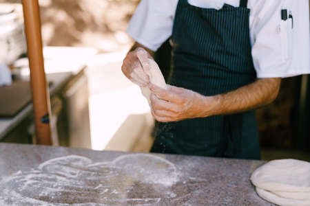 Chef's hands close-up. Prepares the dough for pizza, rolls out in round shapes with his hands. High quality photo Stock fotó