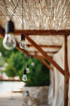 Unpluged garland of incandescent bulbs under the thatched ceiling.